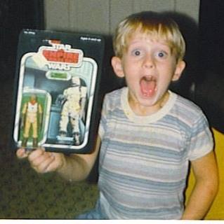 The author as a boy receiving Bossk the Bounty Hunter, the same look he has the first time seeing any new Star Wars film in the theater.