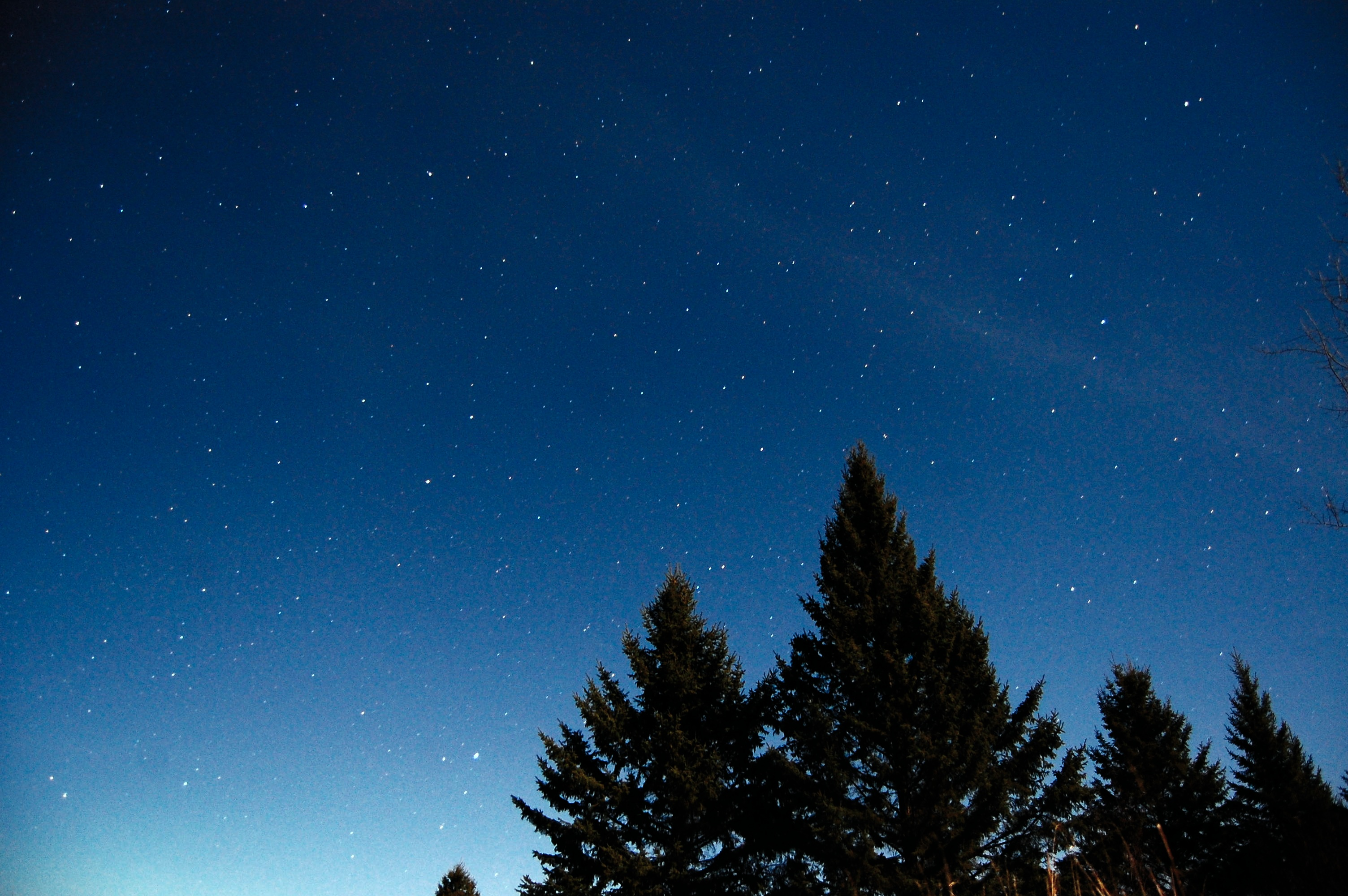 A night time sky with light from a full moon.