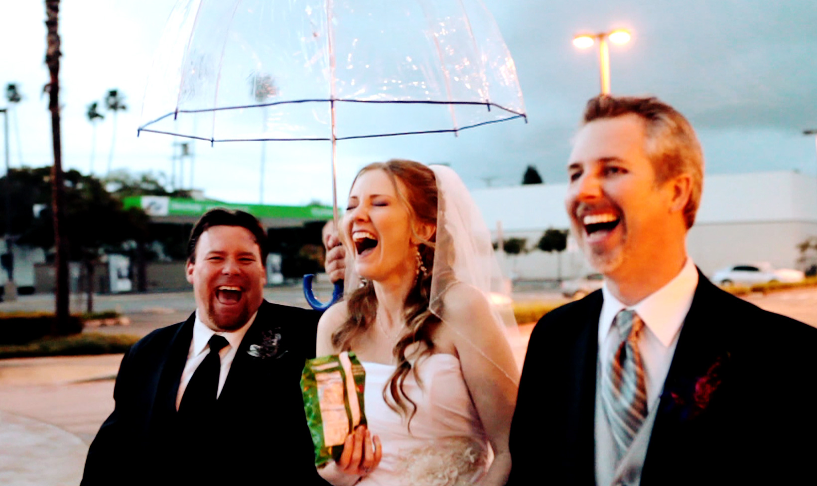 bride enjoying herself in the rain eating chips under an umbrella