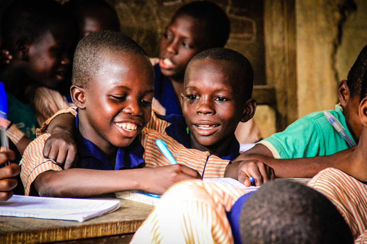 Two little boys in grade 1 at Ilaje Community School, laughing together in the safe environment of their classroom, despite the many challenges they face at home.
