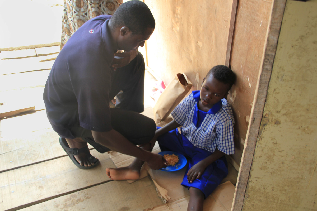 Peter, the Coordinator of our work in Nigeria, feeds a seven-year-old boy in Ago Okota. Paralyzed by hunger, the boy was too weak to feed himself.