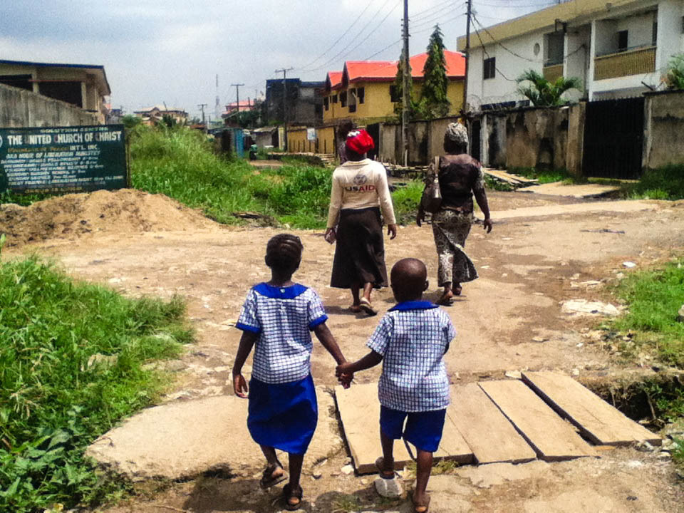 In Ago Okota, Gift (7) and Elijah (5) walk hand in hand towards their home.