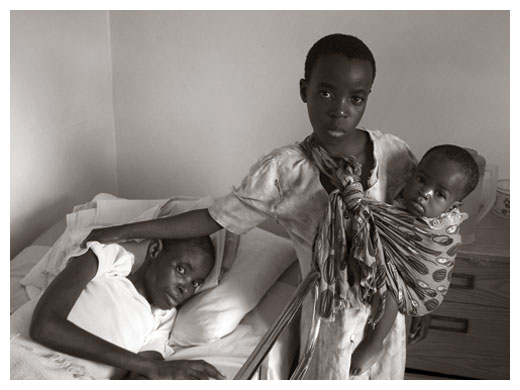 A child carrying her sibling and visiting her sick mother in a clinic near Kabwe, Zambia.