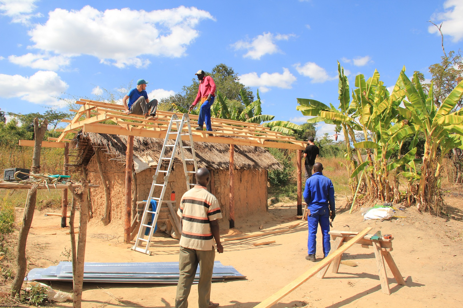 Devon in Zambia (sitting on the roof). Devon supported the Regional Support Team through maintenance and community home repairs with our visiting teams.
