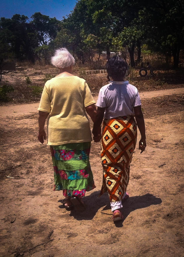 Oumie walking hand in hand with a Care Worker in one of our most vulnerable communities