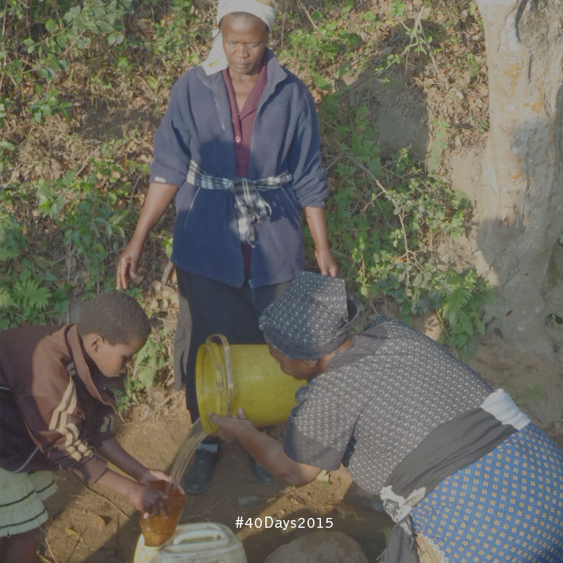 Care Workers in Swaziland help a young girl fetch water