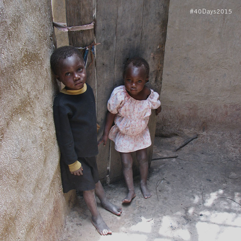 Two siblings in rural Zambia stand in their home that has been ravaged by the rainy season.