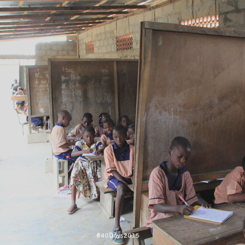 Many grades are taught, separated by chalkboards, in Nigeria