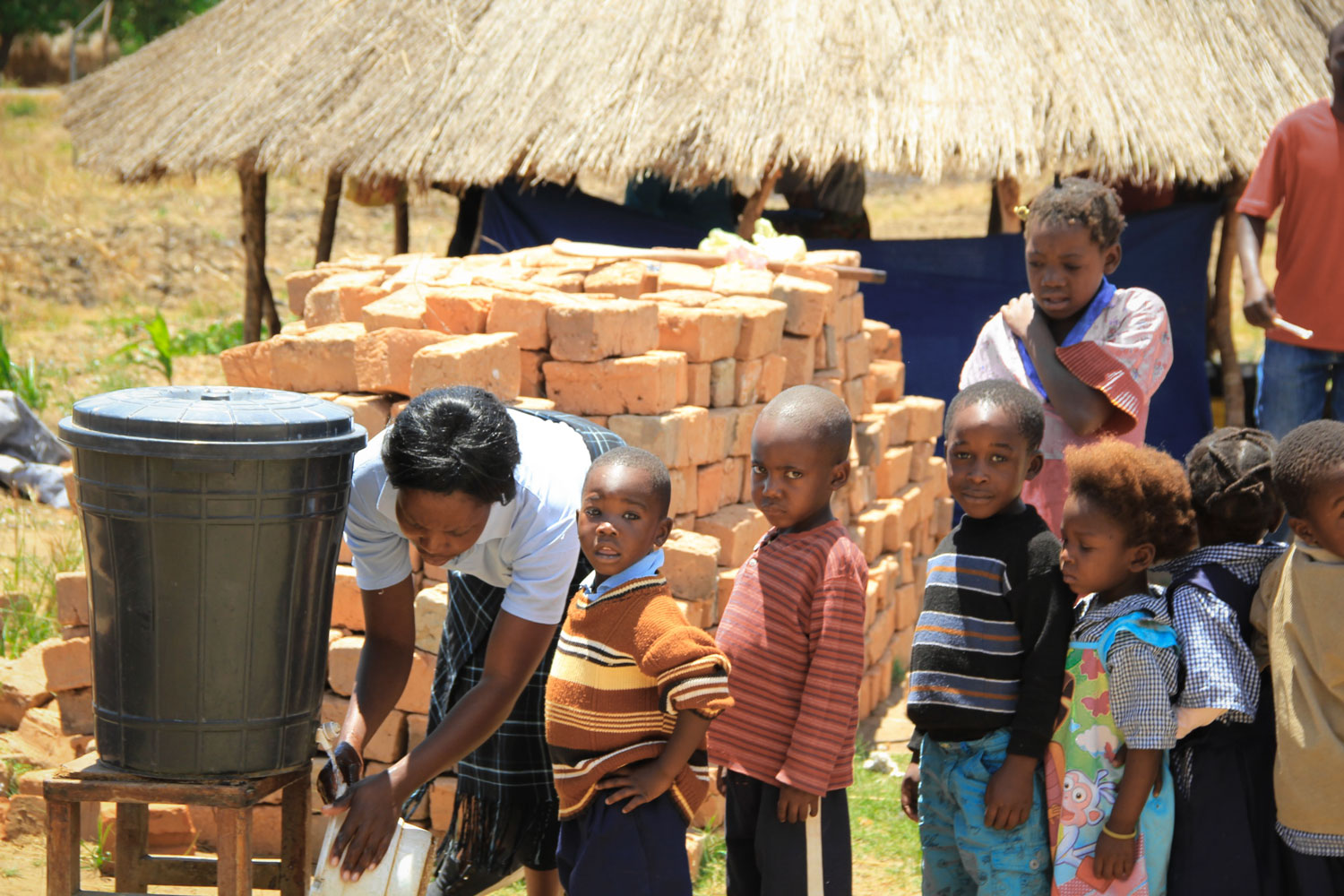 The children wait patiently as one of the Care Workers fills up a bucket of water.