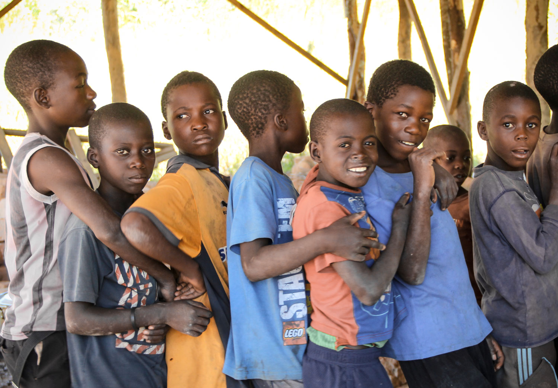 Children wait patiently in line to wash their hands.