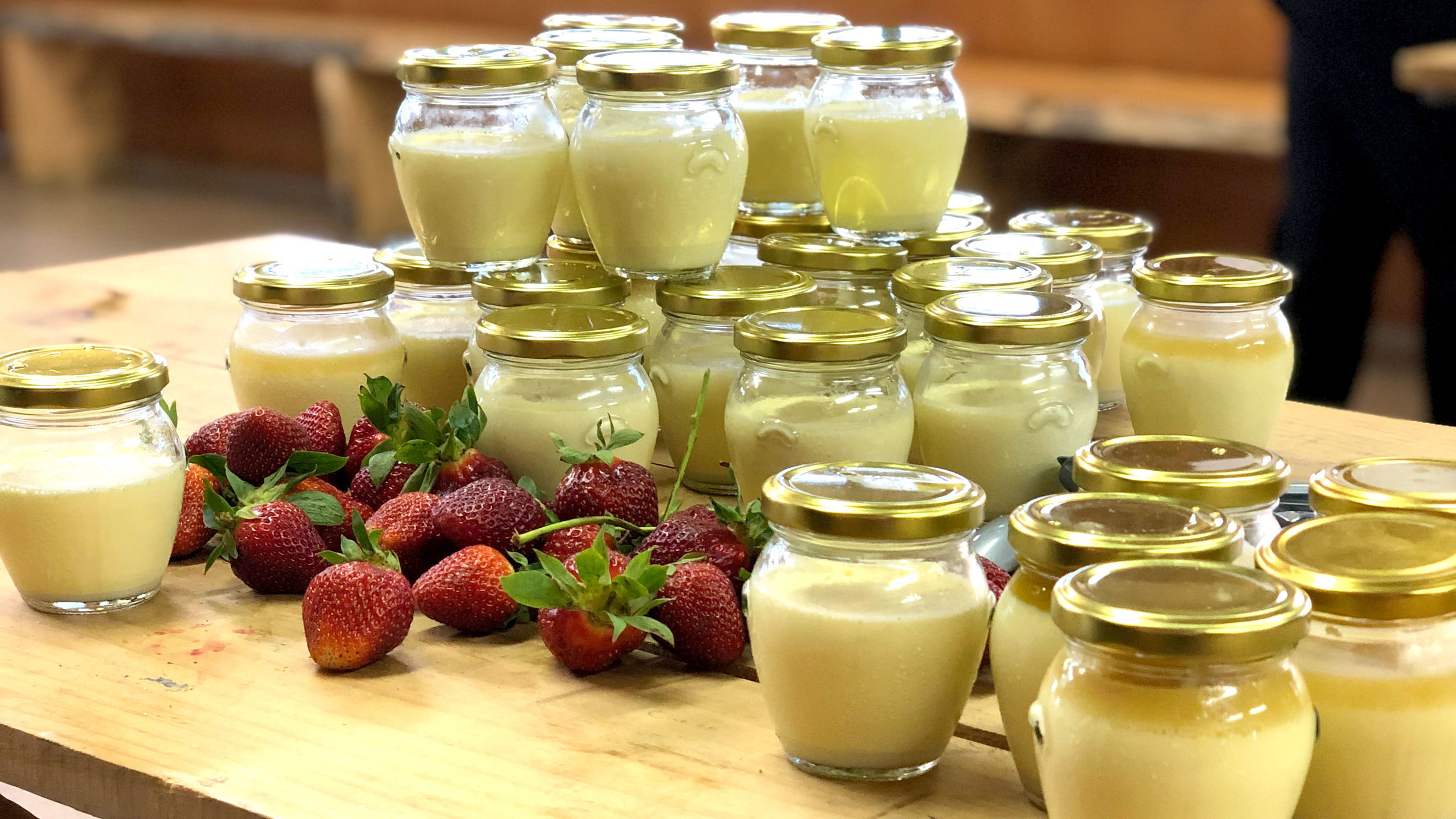 Jars of vanilla panna cotta and strawberries