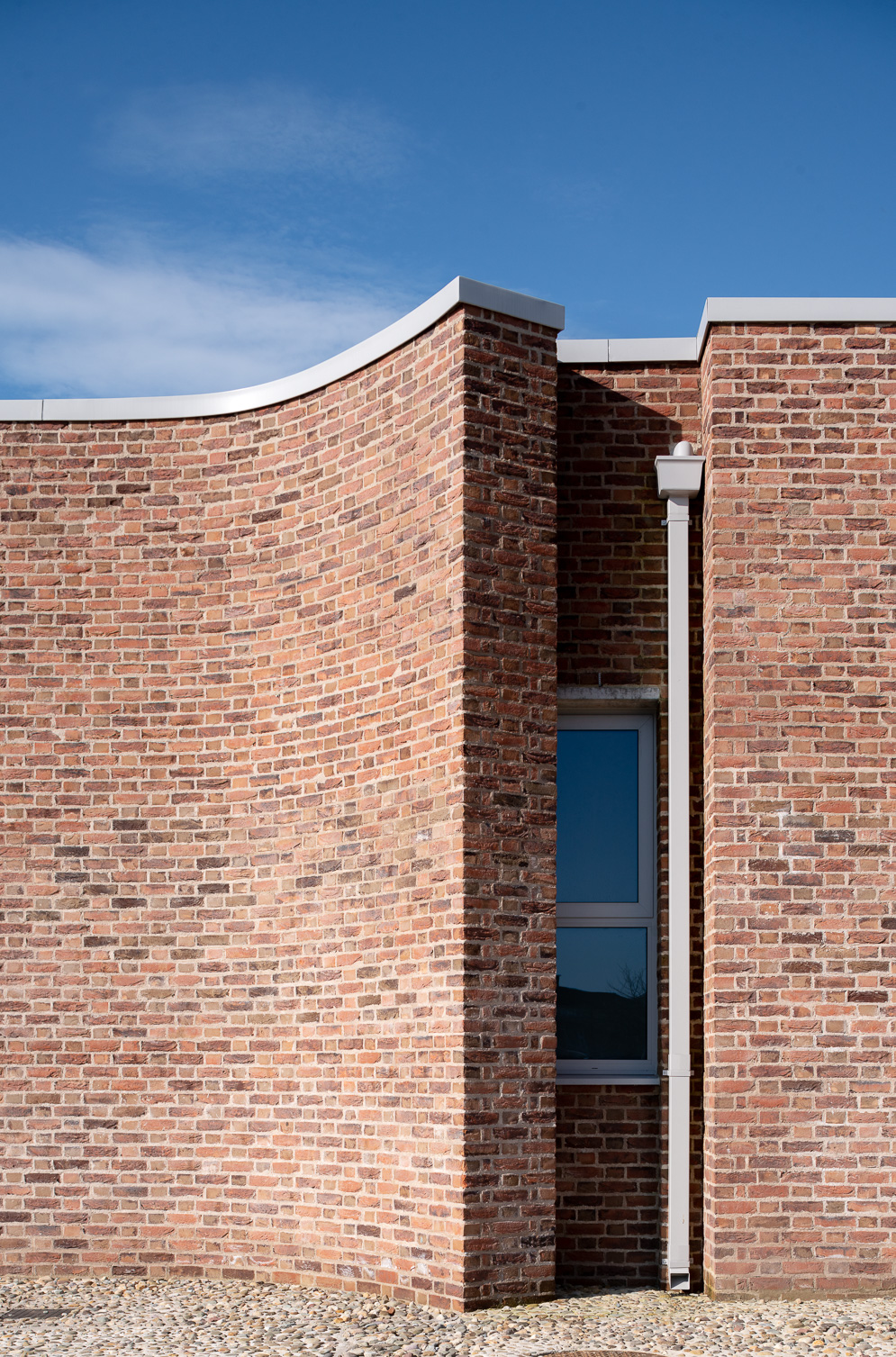 Curving handmade brick facade using a lime mortar and a flemish bon, with a local cobble groundscape.