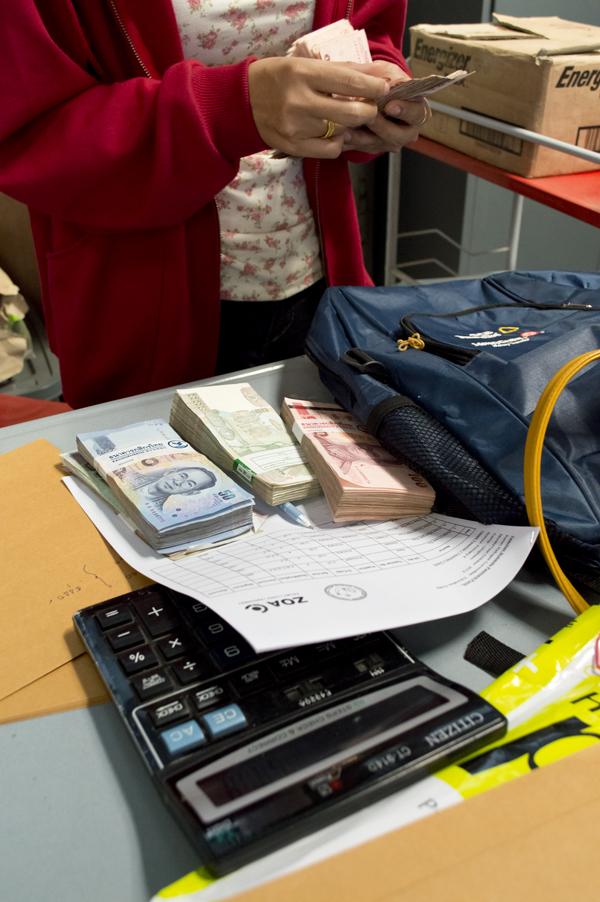 Geld tellen voor de uitbetaling van de maandelijkse leraren vergoedingen in Umphien kamp.