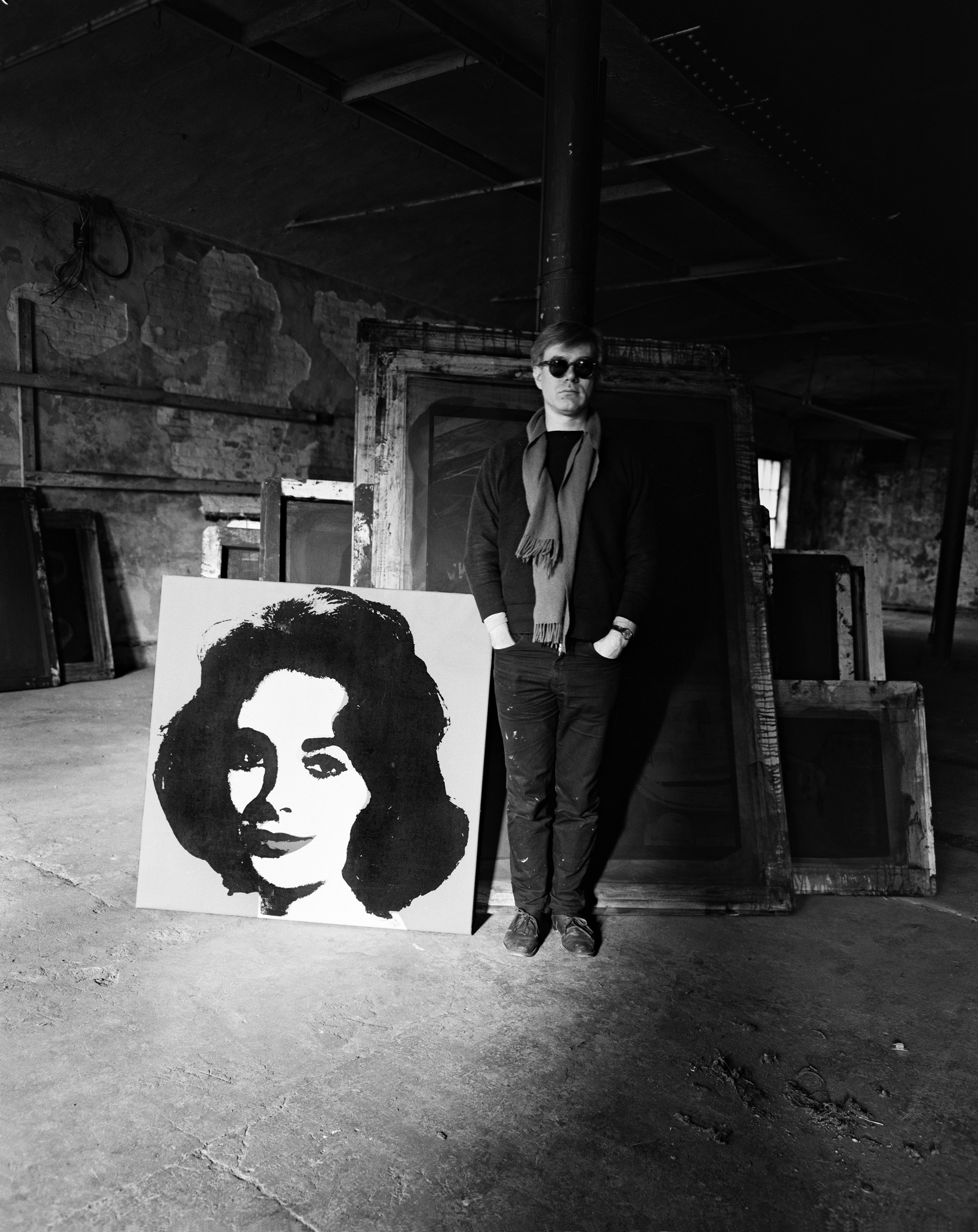 Evelyn Hofer,  Andy Warhol standing in the factory with a Liz painting and several screens in the background , January 29, 1964, gelatin silver print, 14 x 11 in. The Andy Warhol Museum, Pittsburgh; Founding Collection, Contribution The Andy Warhol Foundation for the Visual Arts, Inc, TC31.115..8. Image provided by the estate of Evelyn Hofer