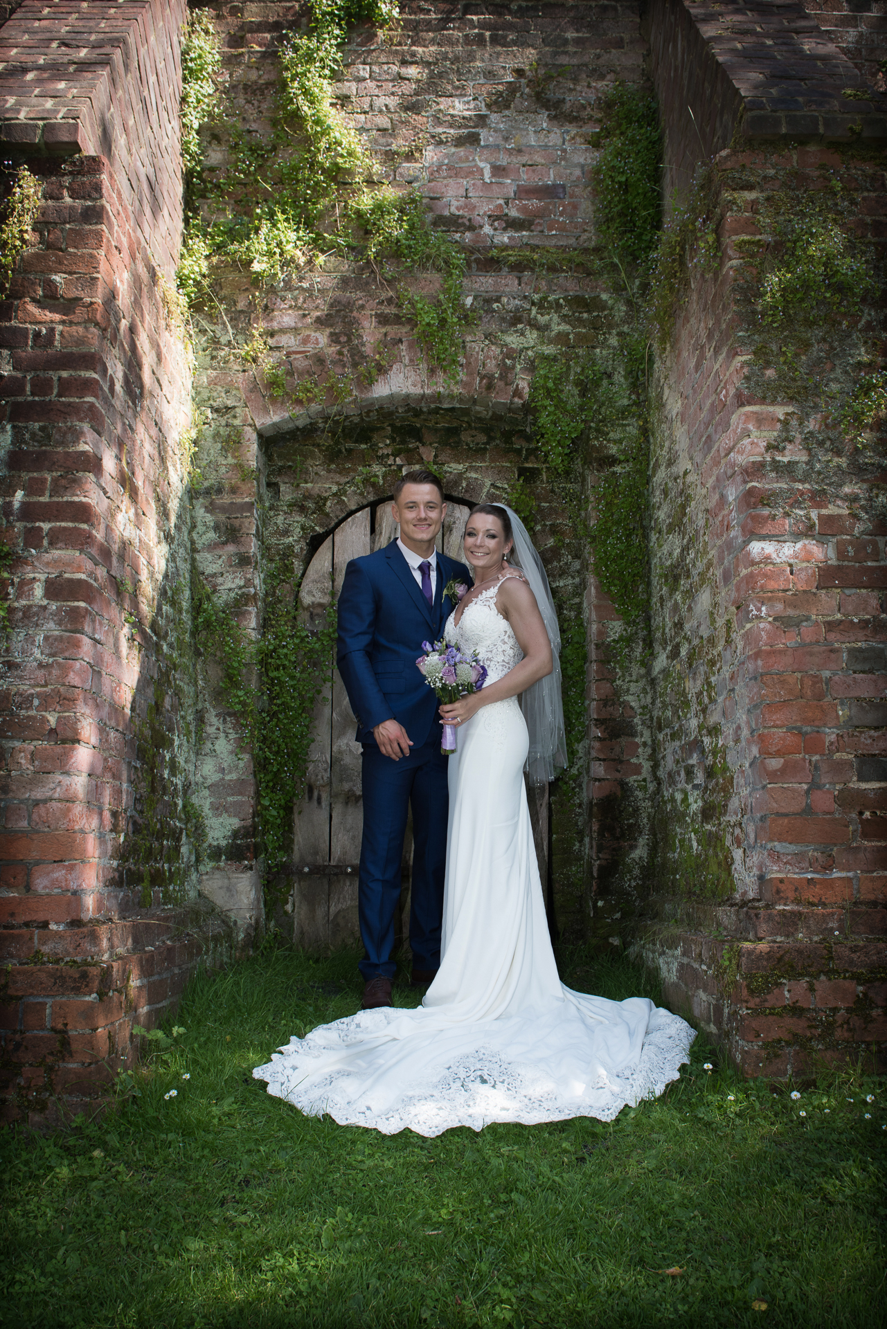 Bride & Groom pose at the Ufton Court garden wall