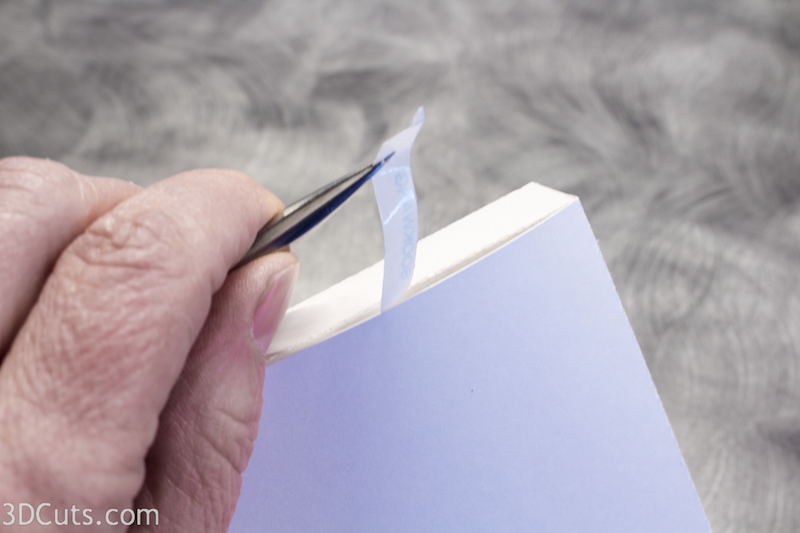 I use needle nose tweezers to peel the backing off the Scor-Tape after the paper is in position. I get better placement using this technique.