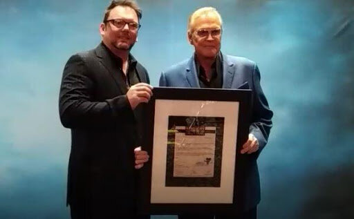Lee Majors accepting his confirmation for induction letter from HOF Executive Director Anthony Hudson.