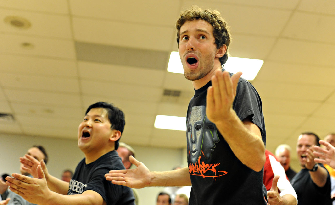 "Tyler Martin, center, and Hisaki Miura, left, strike a ""barbershop squat"" pose during a June 2013 rehearsal at Memorial Hall in St. Charles. Photo by Joel Currier"