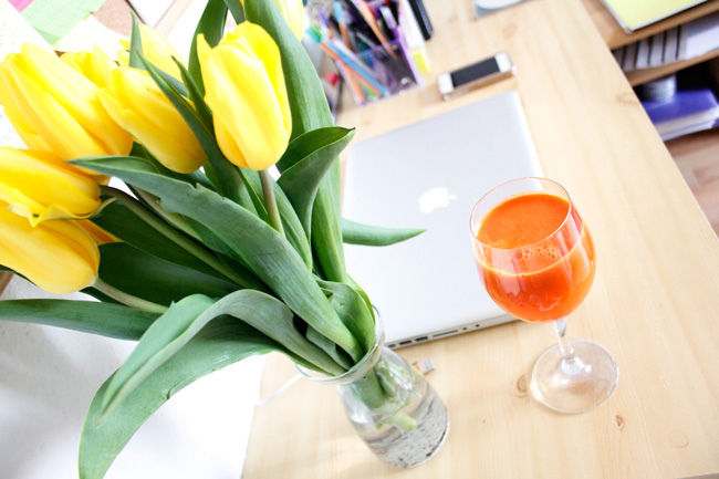 Bright workspace with yellow tulips and fresh carrot orange ginger juice.