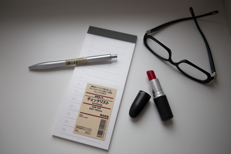 MUJI pen and paper ,  lipstick , & glasses.