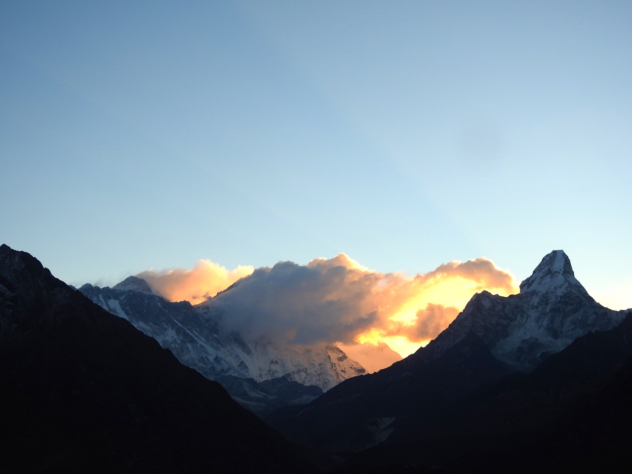 Sunrise in the Himalayas. Clouds and snow blow off the peak of Mt. Everest. Ama Dablam is at the far right. Lhotse is in the middle, obscured by clouds.