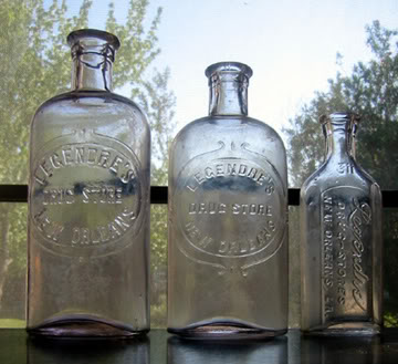 Vintage Glass Bottles on a windowsill make for great decor. Perfect for photographs, cut flowers or filled with buttons or pebbles or anything else.