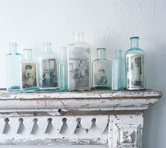 Vintage Photos in Glass Bottles. Vintage photos displayed in Vintage bottles line this white fireplace mantel.