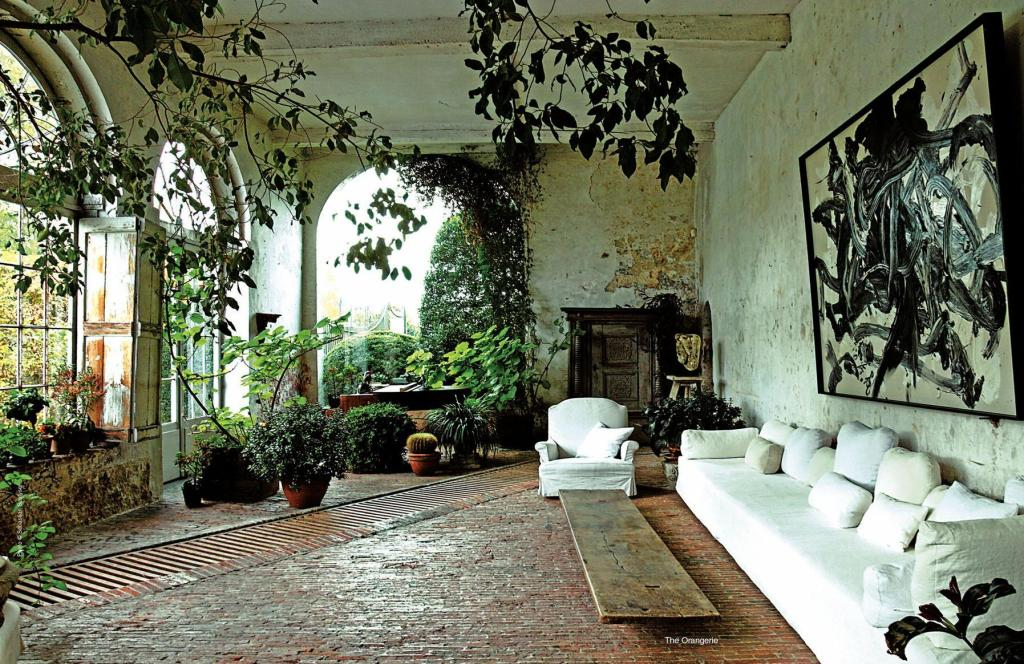 Photography Sebastian Scutyser. This sun room enclosed porch with slanted brick flooring and grated drain is perfect for a room full of indoor plants. You won't have to worry about water overflow and you and your plants can always be happy.