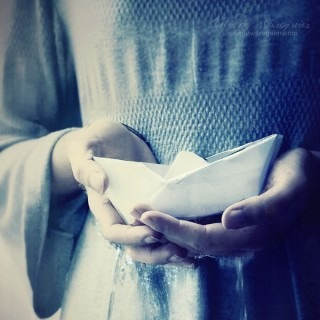holding a paper boat