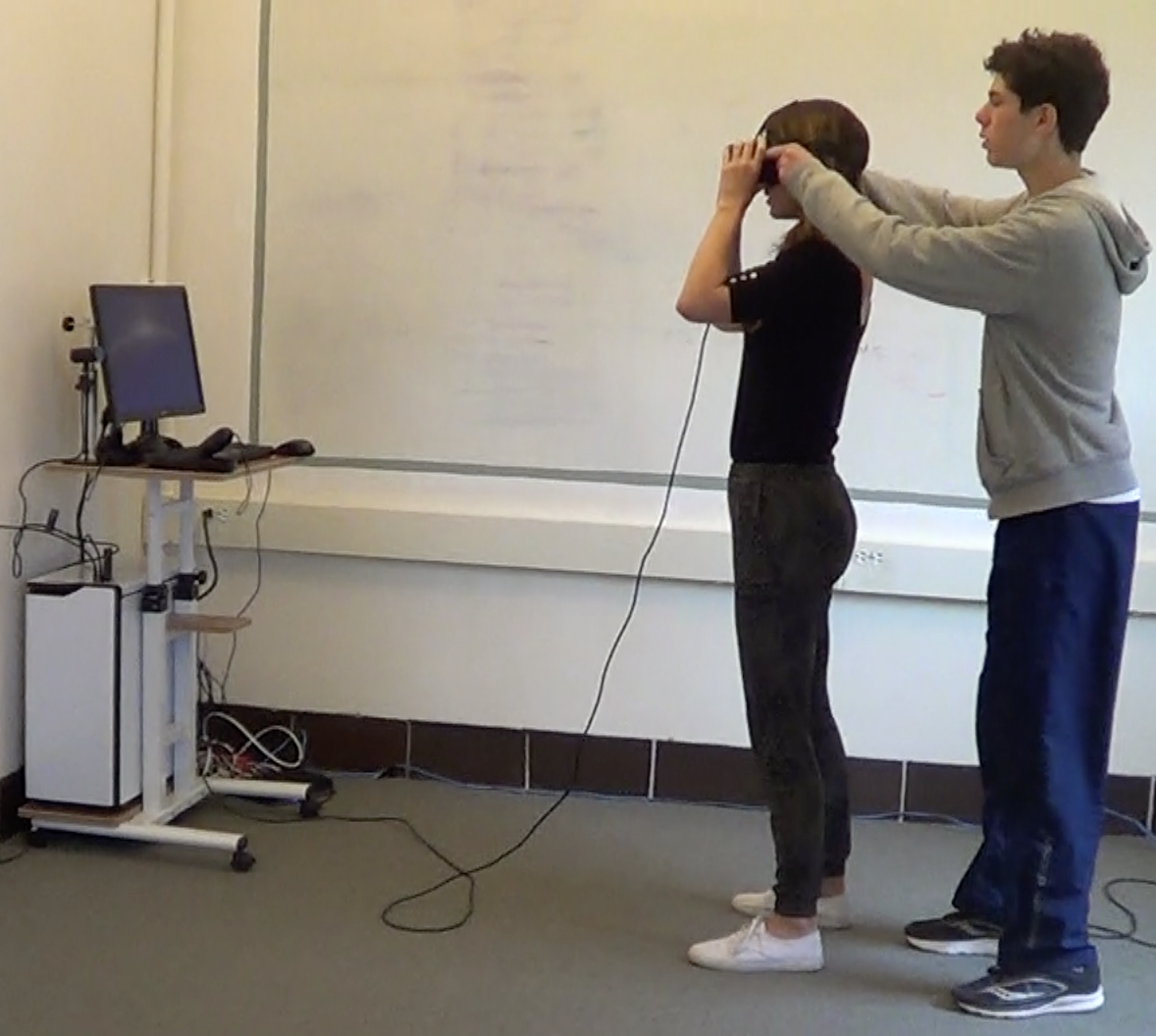 A VR lab facilitator helps a user adjust her head-mounted display