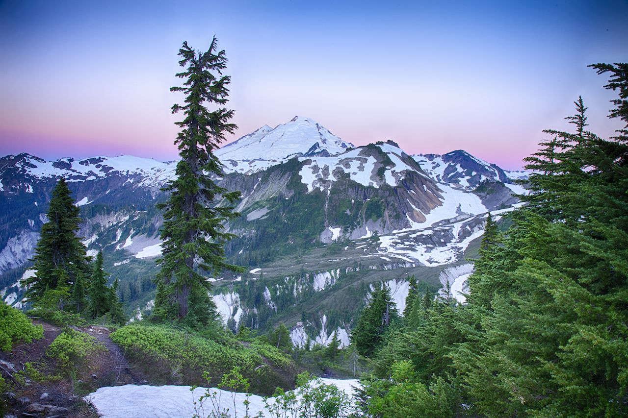 The first rays of the sun light up the sky around the peak of Mount Baker.