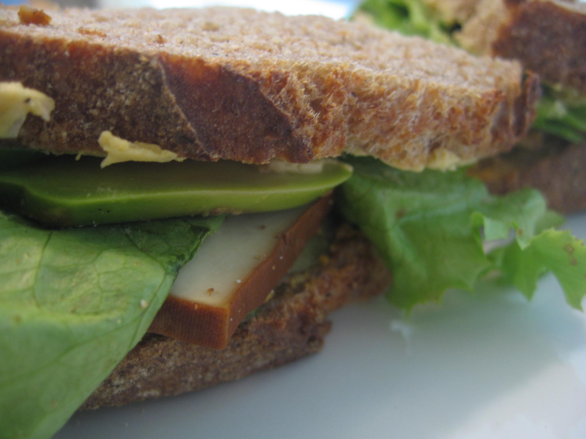 Organic Wholegrain Spelt Sourdough with smoked tofu, lettuce, hummus, roasted veggie spread, and a few avocado slices.