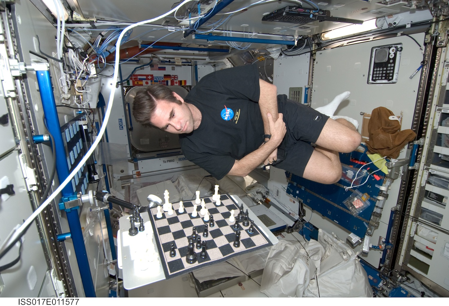 The arm holding Nasa astronaut Greg Chamitoff's chess board attaches to the blue handrail using a Handrail Clamp Assembly. That keeps the chessboard in place, but the chess player...?  Source:  Nasa