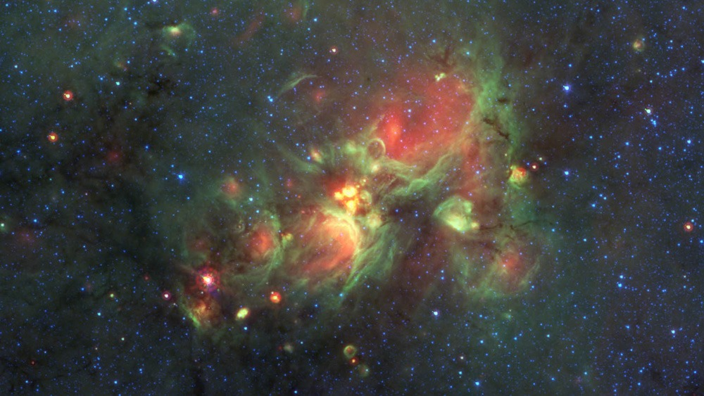 The yellowballs at the center of this image are glowing shells of gas surrounding newly born large, hot stars. Credit:  Nasa/JPL-Caltech