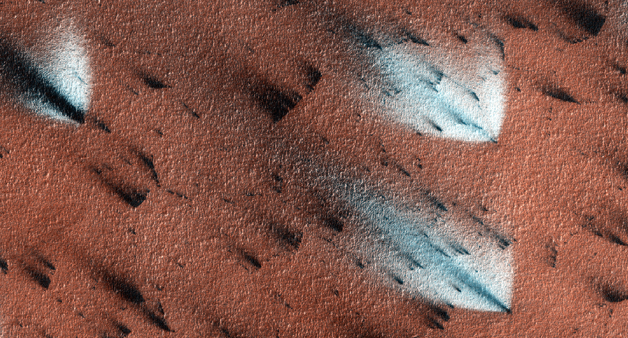 """Carbon dioxide ice blankets Mars during the winter. Dust clouds puff out ofthe ice during the spring thaw to form these dark """"fans"""". Once the ice sublimates away the dust blends into the Martian surface and the fans disappear. Planet Four crowdsources maps of these dust fans to study Martian wind patterns. Credit:  Nasa/JPL-Caltech/University of Arizona"""