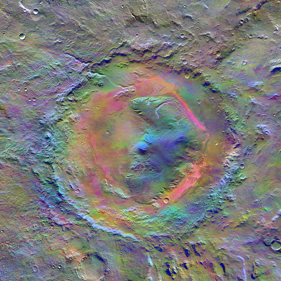 Mars Odyssey's view of Gale Crater. The enhanced color image from the Themis camera shows the distribution of minerals on the surface. The pink shading is wind-blown dust that partially covers basalt (purple) created during the asteroid impact. The bluish regions at the peak of Aeolis Mons (Mount Sharp) may be a different mineral that Curiosity may identify later in its journey.  Credit:  Nasa/JPL-Caltech/Arizona State University