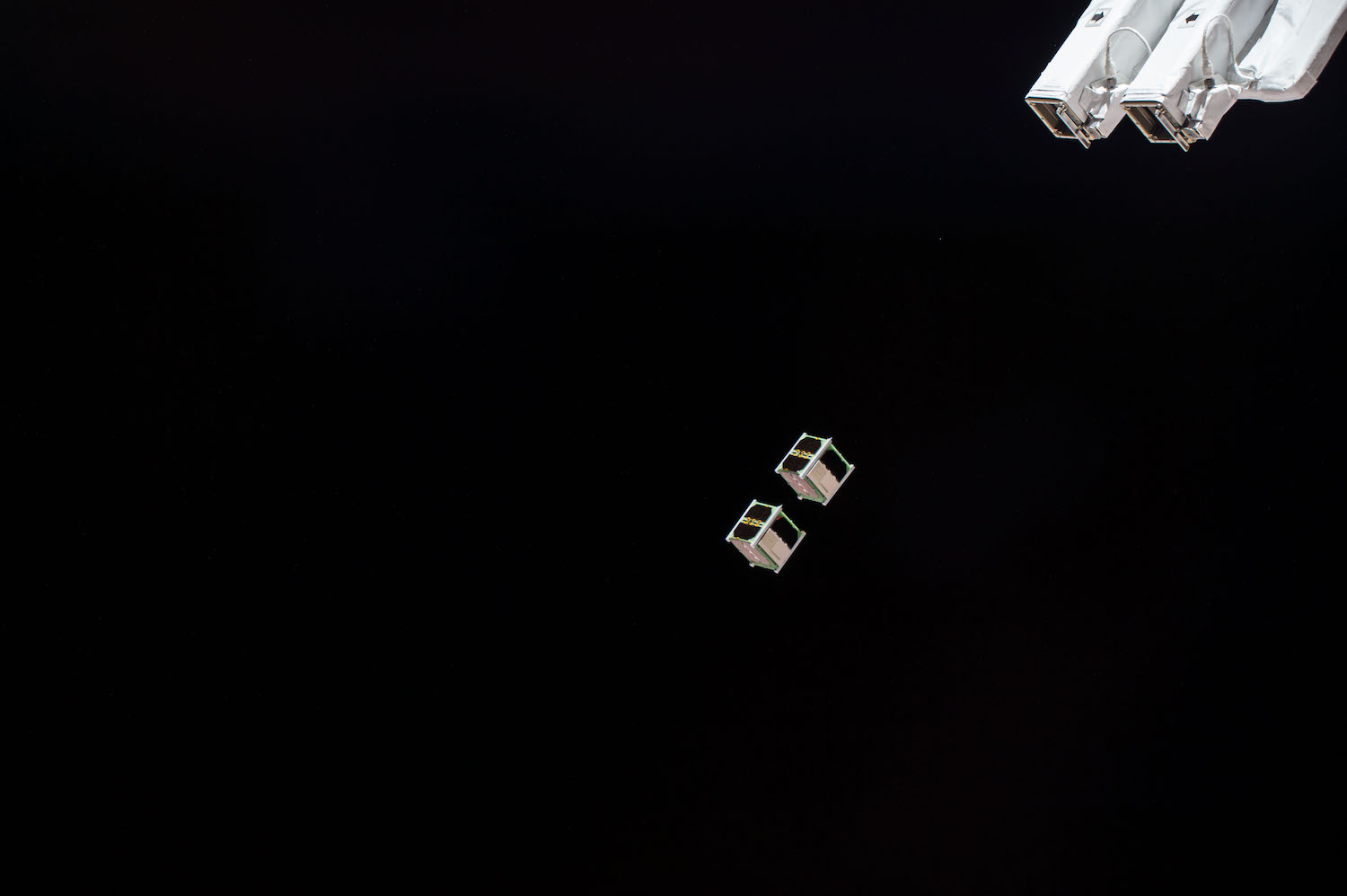 Two of the five Birds CubeSats floating away from the International Space Stations. Amateur radio operators around the world will communicate with the small satellites to help researchers exploring communications constellations.  Credit: Nasa