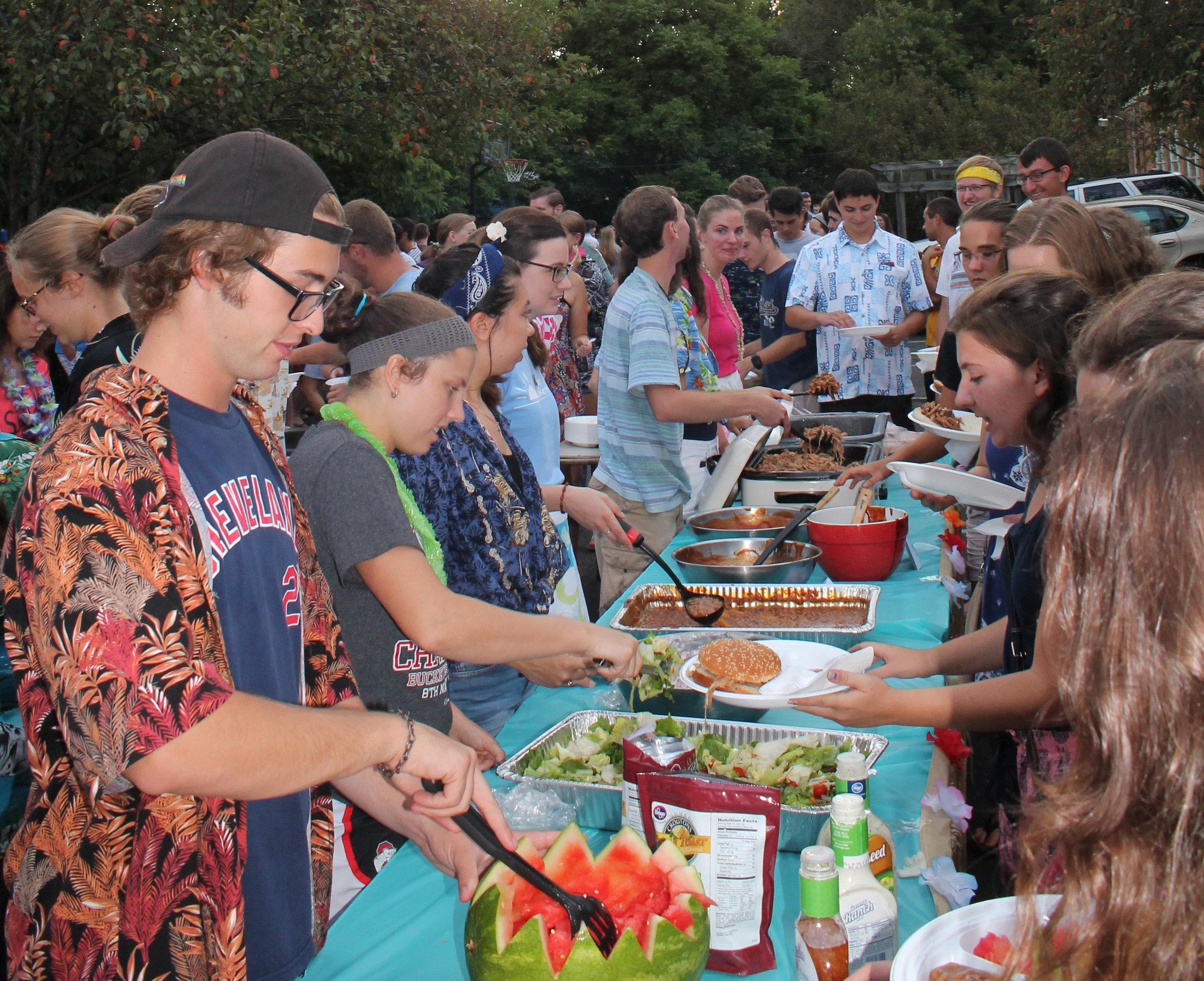 Jacob Ritchey (far left) helps serve food at SPO's annual Hog Roast.