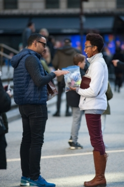 Isabelle Maina, SPO Missionary at Seton Hall, engages in conversation with a pedestrian, offering him a rosary and inviting him into the Cathedral.