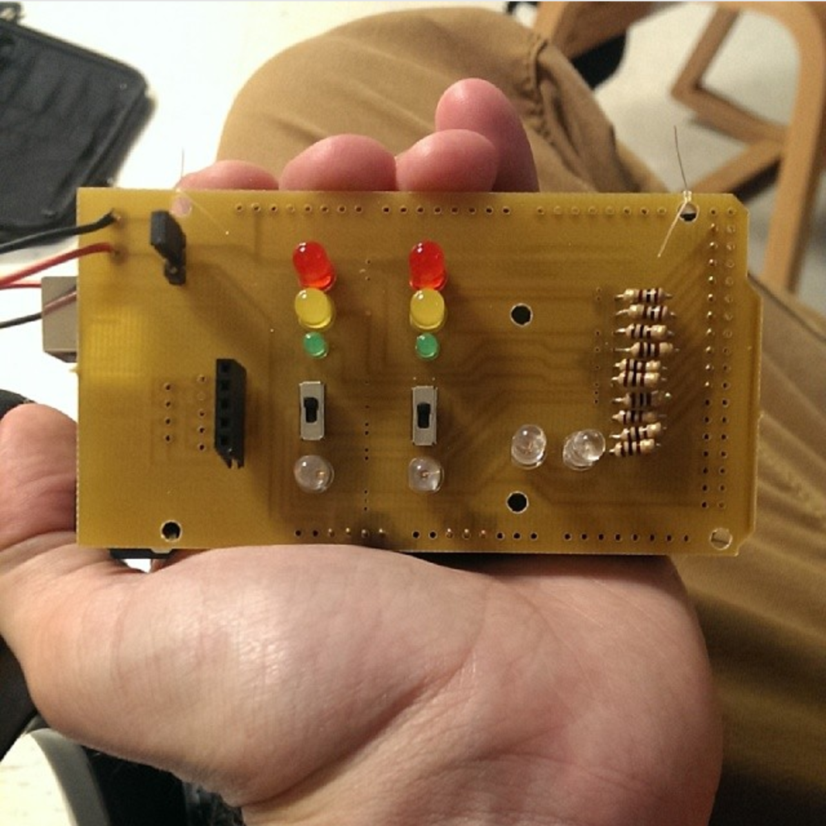 The custom controller built for this application on an Arduino platform. The lights indicate the state of each pair of traffic lights in each direction, and the switches control the time-priority of traffic going each direction respectively.