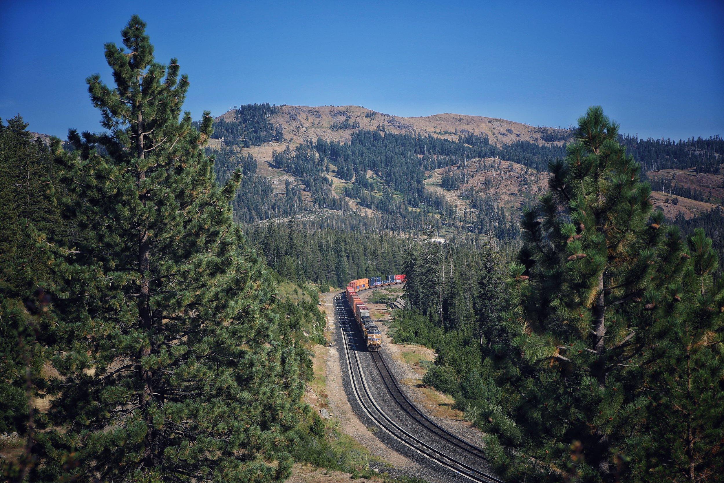 Long train chugging through the Sierras in California.