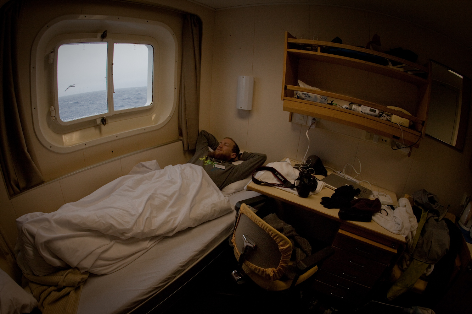 Nic in bed as an albatross soars by our window on the Drake Passage.