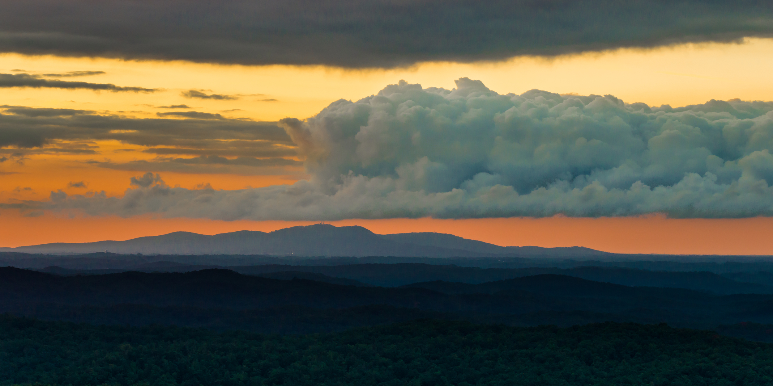 blue mountains with yellow and orange sky