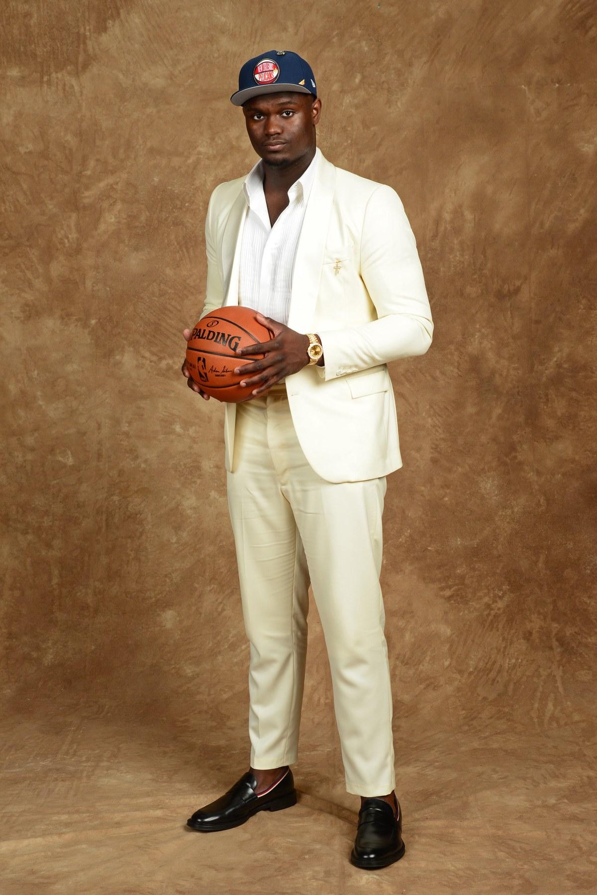 Zion Williamson Abrimos a galeria com a grande estrela da noite. Escolha número do draft, Zion mostrou que além de uma promissora carreira na NBA, ele também promete dar o que falar no quesito moda. Com um traje de lapela  shawl  (arredondada) - que seguiu suas medidas com precisão e um discreto  loafer  sem meia, Zion aliou simplicidade com bom gosto e por isso foi um dos mais elegantes do evento.