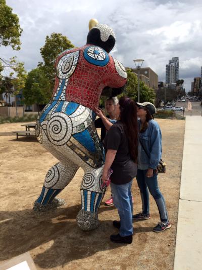 """Ilse Cordoni, Consuelo Sierra, and Sherry Tobin examine Niki de Saint Phalle's """"Baseball Player,"""" on the San Diego waterfront."""