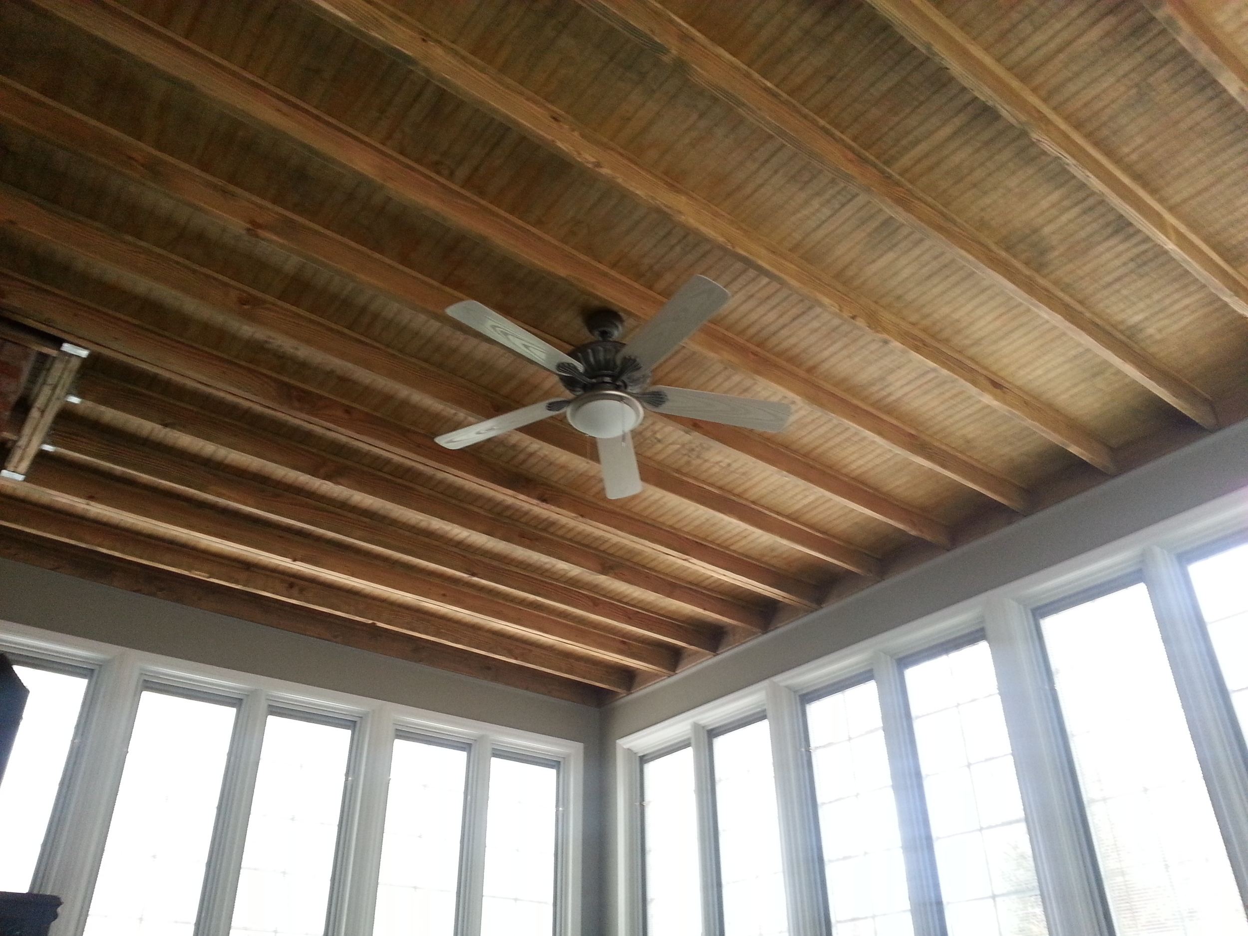 Custom sun room with stained exposed rafters. Installation by Groundswell Contracting