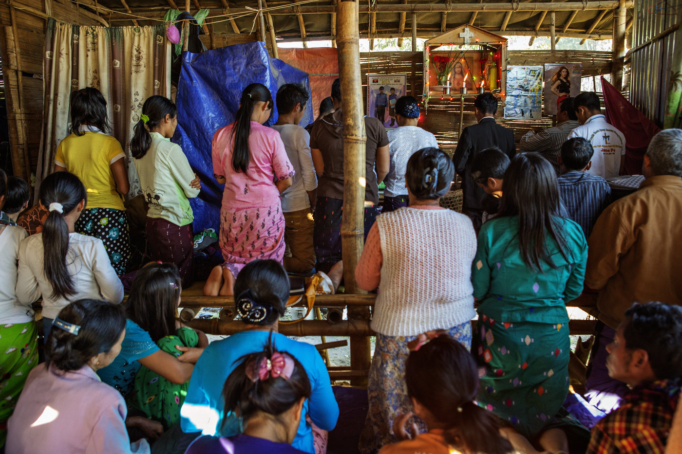 Internally displaced Kachin refugees attend a small Christmas Day Catholic service in a bamboo home at Jeyang refugee camp December 25, 2012 outside of Laiza, Kachin State in northern Myanmar. The camp is home to app. 7500 refugees.
