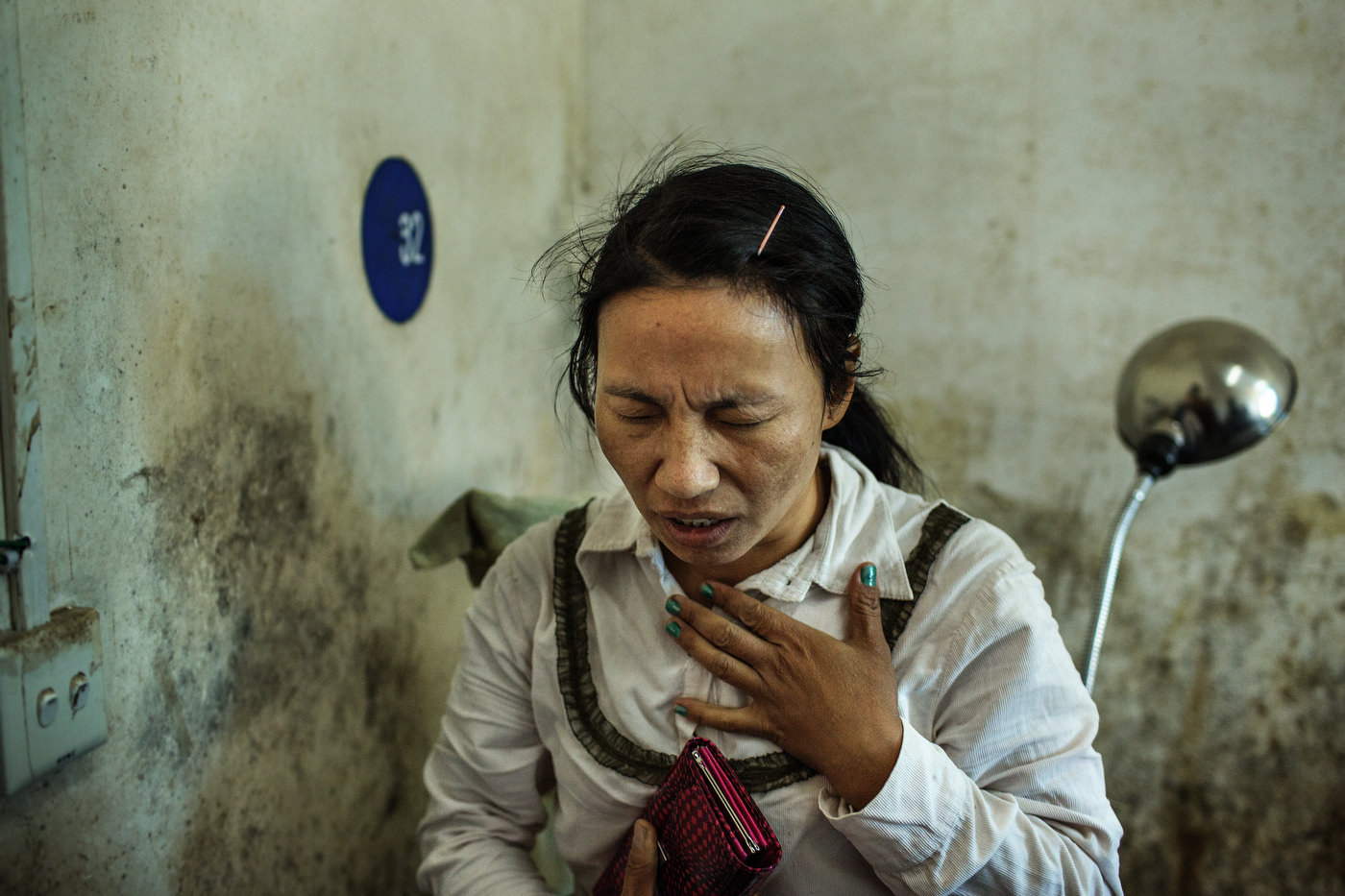 A bigger sister of Lamung Kailing prays while her little sister is being treated for injuries sustained from mortar shrapnel in Laiza Hospital.