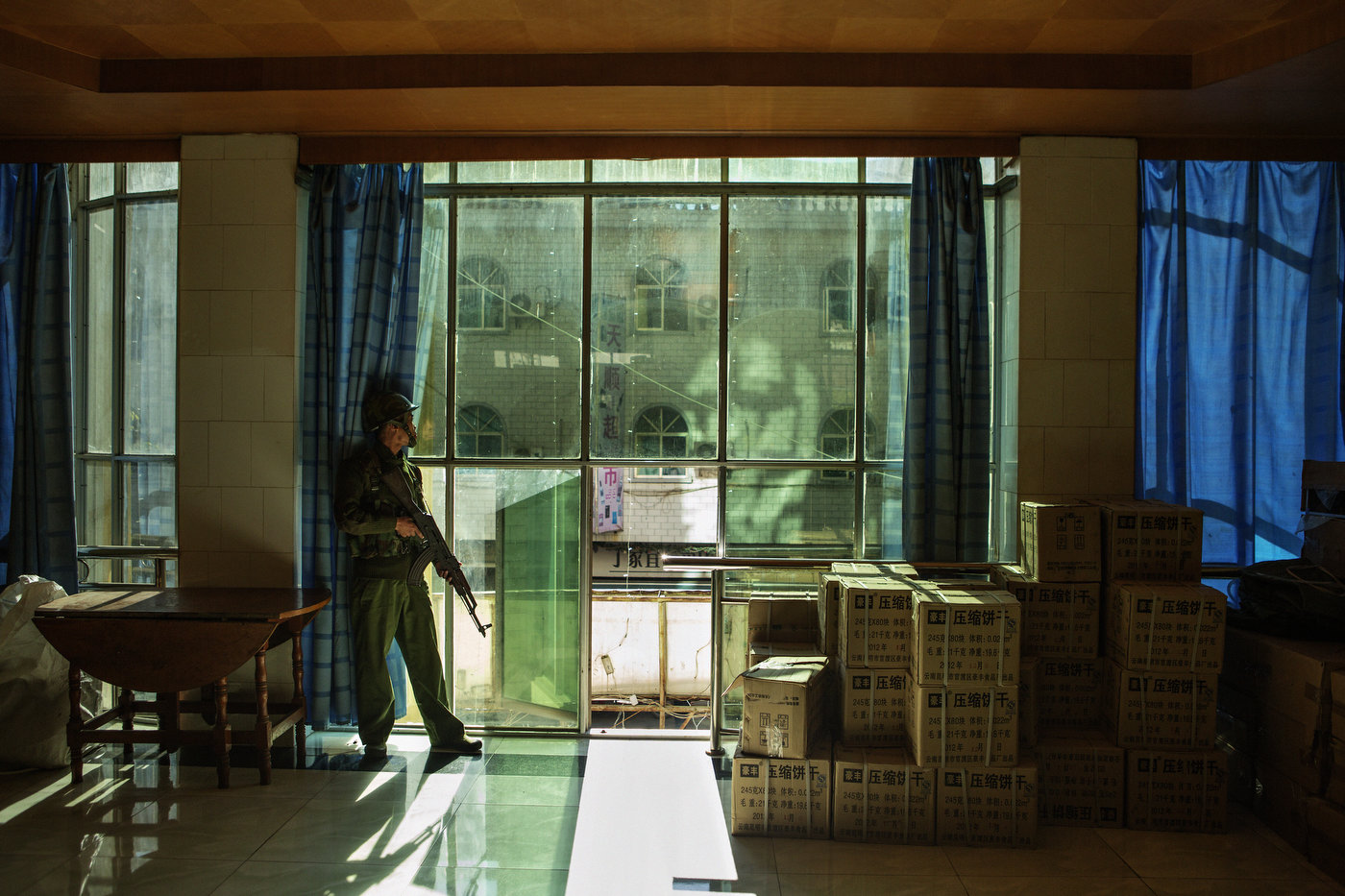 A KIA soldier, who stands guard in Laiza Hotel, looks for Burmese aircrafts attacking outposts in the distance.