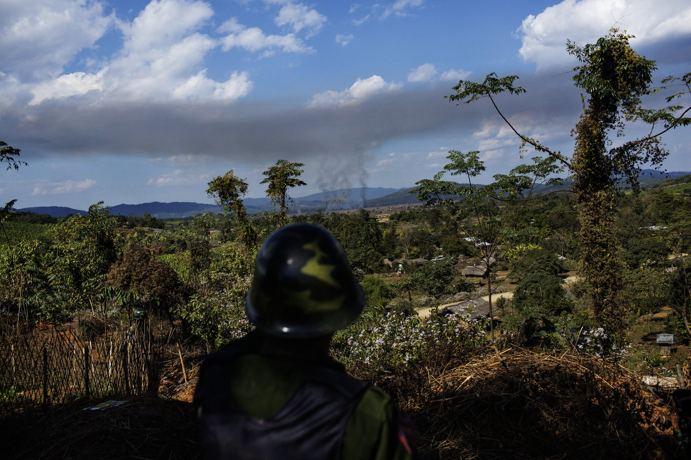 A KIA soldier looks at the shelling by Burmese heavy artillery of the small town of Namsangyang in Kachin State in northern Myanmar.
